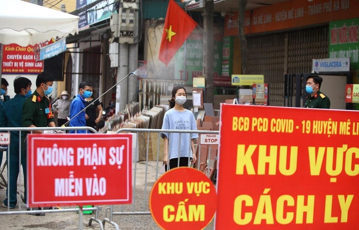 Phun thuốc diệt khuẩn cho người giao hàng nhu yếu phẩm vào khu cách ly tại thôn Hạ Lôi. Ảnh: Minh Quyết/TTXVN)