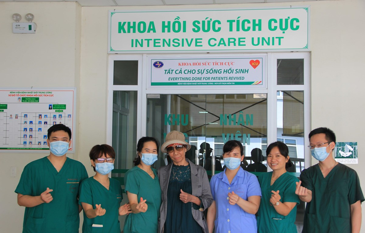 Bệnh nhân 19 chụp ảnh cùng các y bác sỹ Khoa Hồi sức tích cực trong ngày được xuất viện về nhà. (Ảnh: PV/Vietnam+)