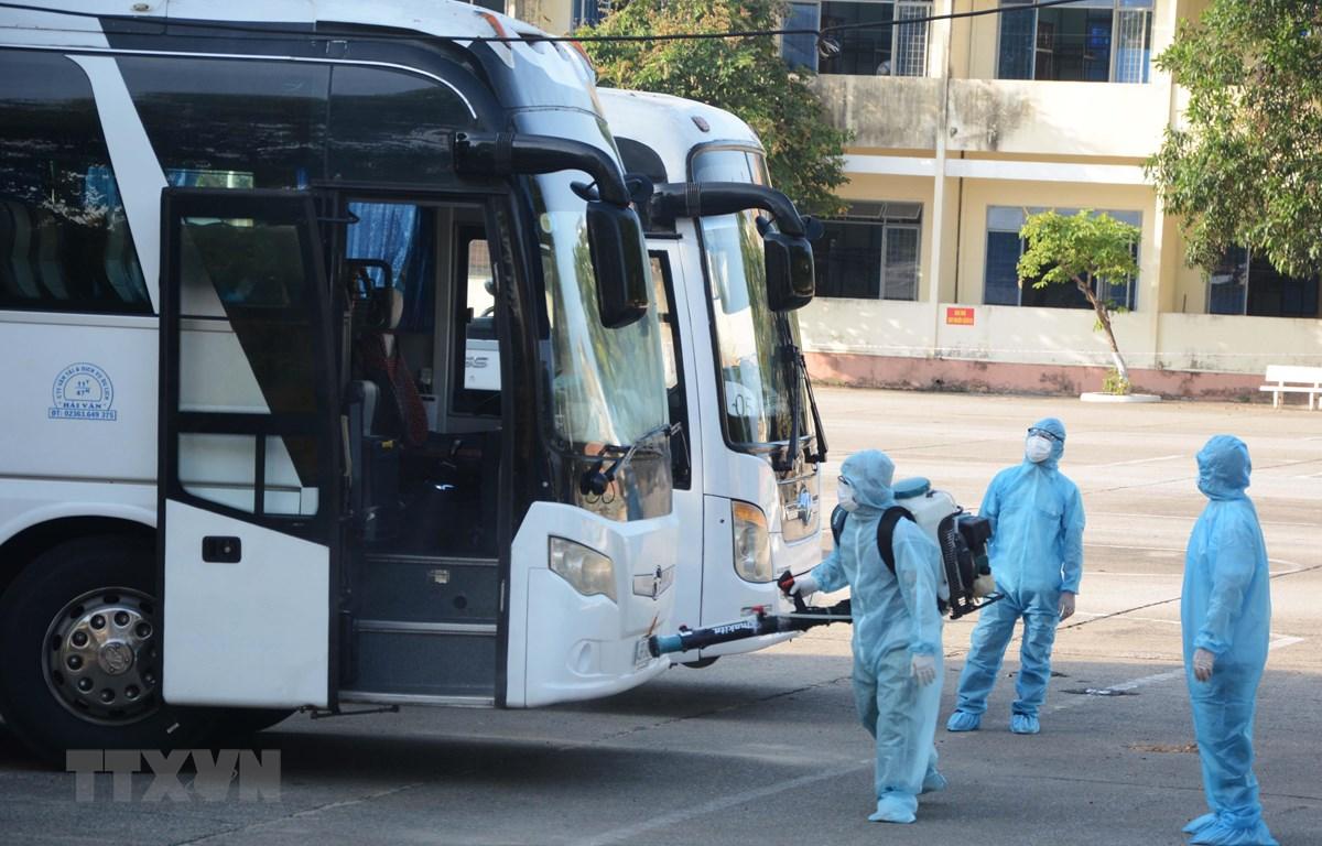 Nhân viên y tế phun thuốc khử trùng vào xe chở công dân từ Hàn Quốc trở về. (Ảnh: Văn Dũng/TTXVN)