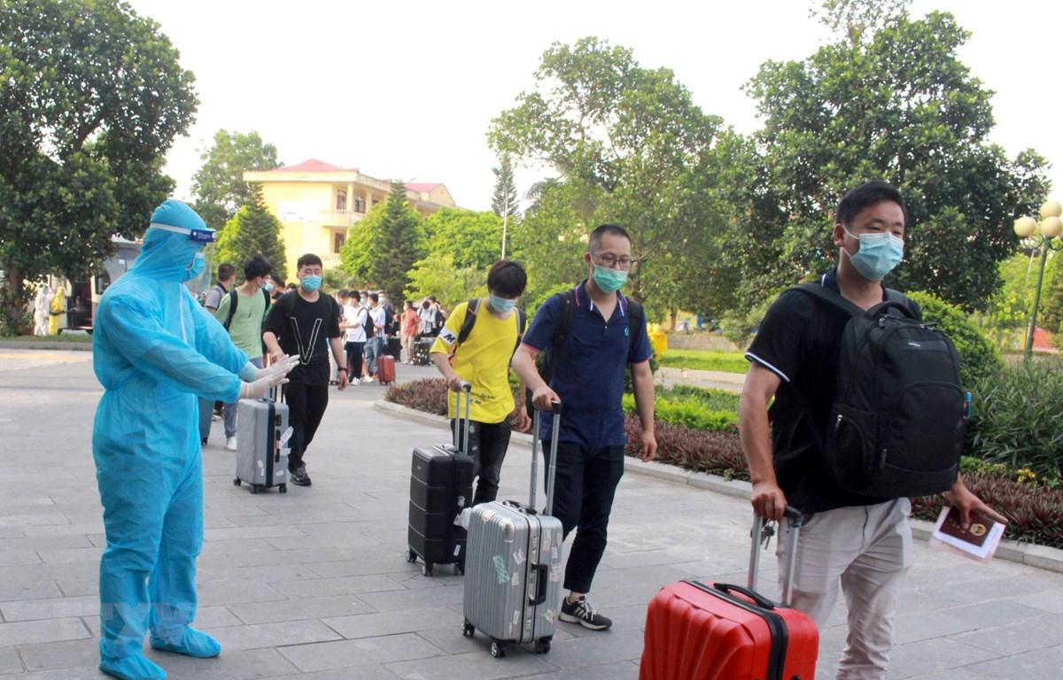 Nhân viên y tế hướng dẫn chuyên gia, lao động nước ngoài đi đường riêng khi vào khách sạn cách ly. (Ảnh: Đồng Thúy/TTXVN)