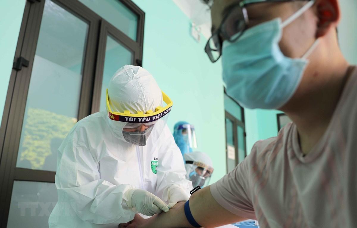 Nhân viên y tế lấy mẫu máu để xét nghiệm nhanh cho người dân tại Trạm Y tế phường Dịch Vọng, quận Cầu Giấy. (Ảnh: Thanh Tùng/TTXVN)