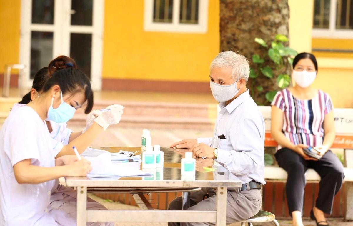 Người về từ Đà Nẵng đến đăng ký lấy mẫu dịch hầu họng để xét nghiệm bằng phương pháp RT-PCR tại Hà Nội . (Ảnh: Minh Quyết/TTXVN)