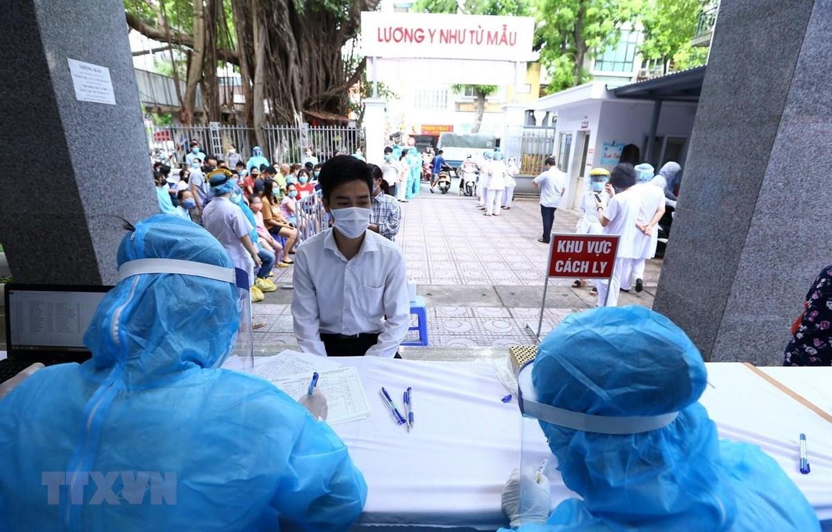 Người dân trở về từ Đà Nẵng đến khai báo lấy mẫu xét nghiệm bằng phương pháp RT-PCR tại Trung Tâm Y Tế quận Hai Bà Trưng. (Ảnh: Minh Quyết/TTXVN)