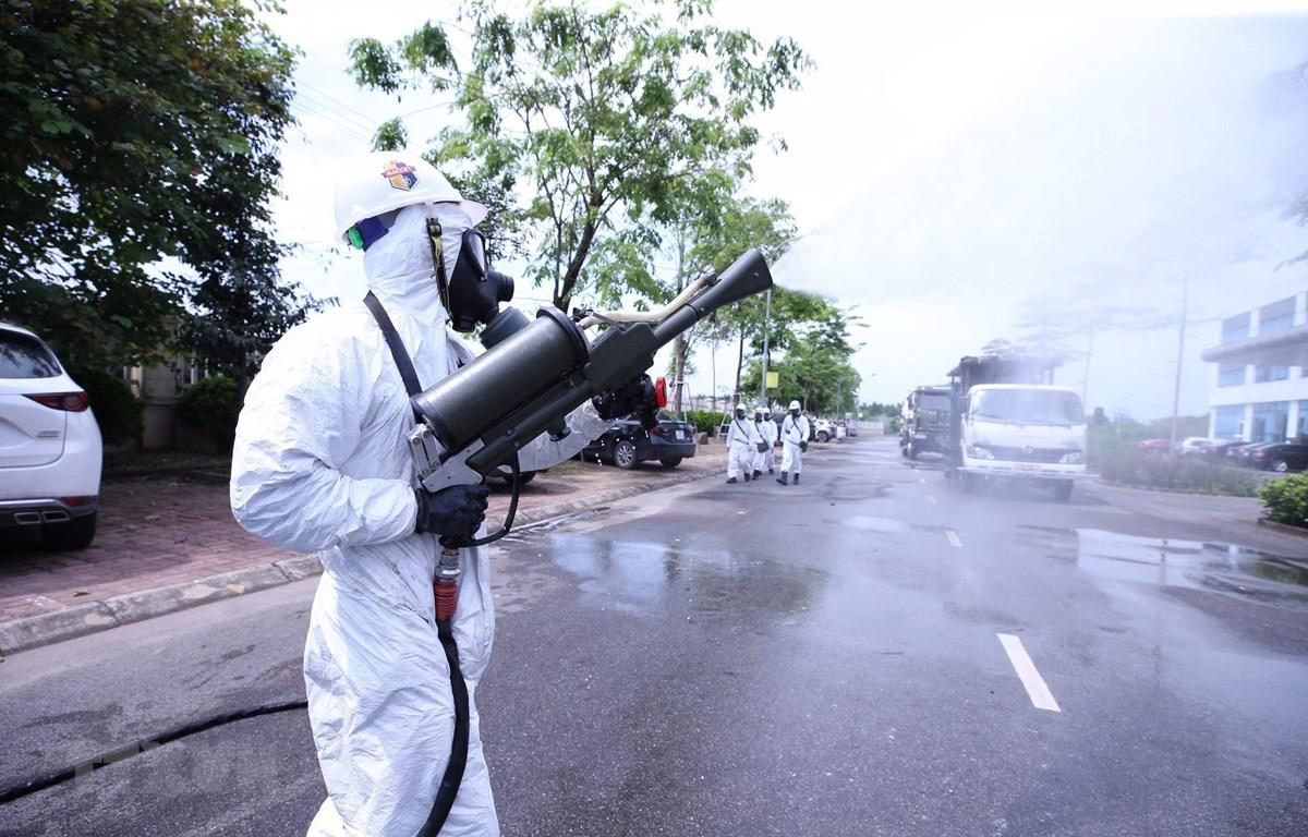 Bộ đội hóa học phun thuốc khử trùng Bệnh viện Bệnh Nhiệt đới Trung ương cơ sở Đông Anh. (Ảnh: Minh Đức/TTXVN)