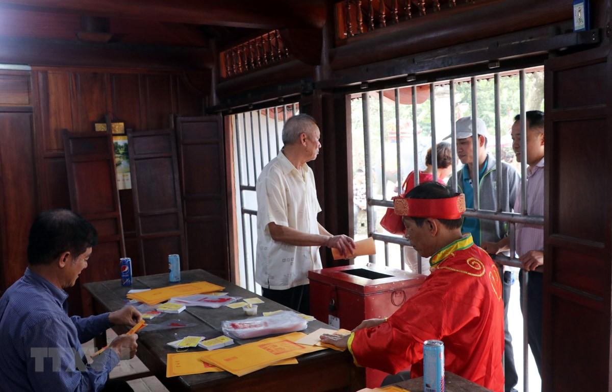 Các cụ cao niên phường Lộc Vượng, thành phố Nam Định (Nam Định) chuẩn bị ấn phát cho nhân dân, du khách. (Ảnh: Văn Đạt/TTXVN)