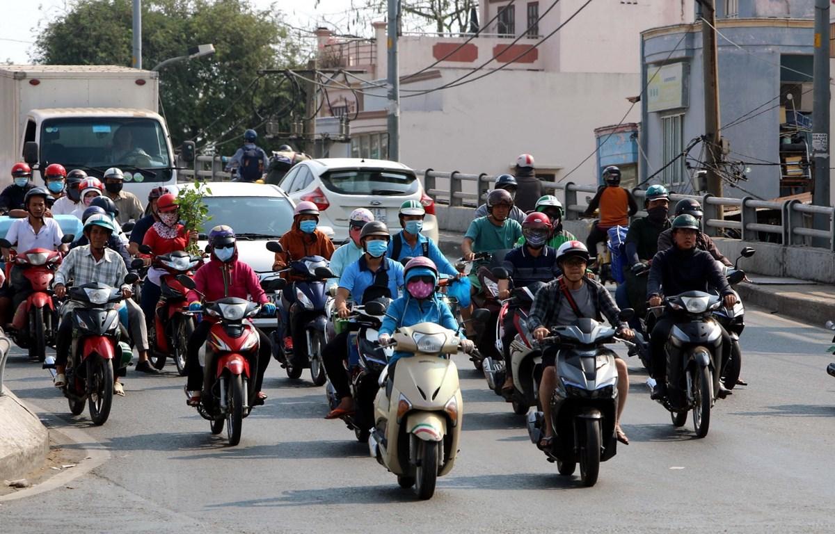 Phần đông người dân Thành phố Hồ Chí Minh đều trùm kín người khi đi ra đường trong những ngày nắng nóng. (Ảnh: Thanh Vũ/TTXVN)