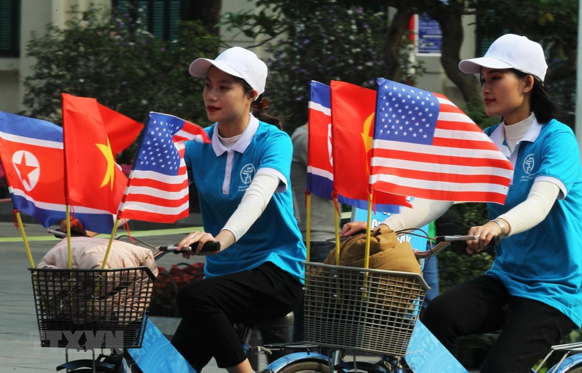 Trong ảnh: Thiếu nữ Việt Nam đạp xe diễu hành với cờ Việt Nam, Mỹ và Triều Tiên trên đường phố Đinh Tiên Hoàng, Hà Nội. (Ảnh: Lâm Khánh/TTXVN)