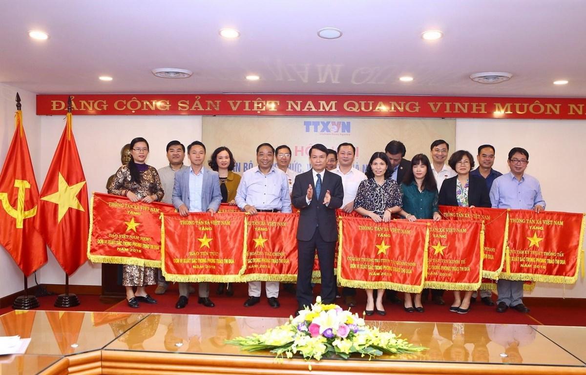 Ủy viên Trung ương Đảng, Bí thư Đảng ủy, Tổng giám đốc TTXVN Nguyễn Đức Lợi tặng Cờ thi đua của TTXVN cho 21 tập thể. (Ảnh: Minh Quyết/TTXVN)