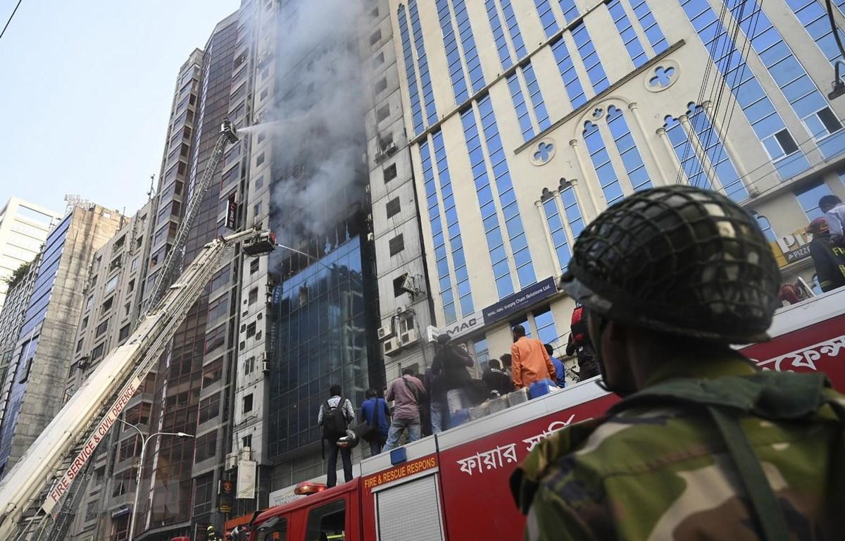 Lực lượng cứu hỏa nỗ lực dập lửa và tìm kiếm các nạn nhân tại hiện trường vụ cháy tòa thương mại 22 tầng ở Dhaka. (Nguồn: AFP/TTXVN)