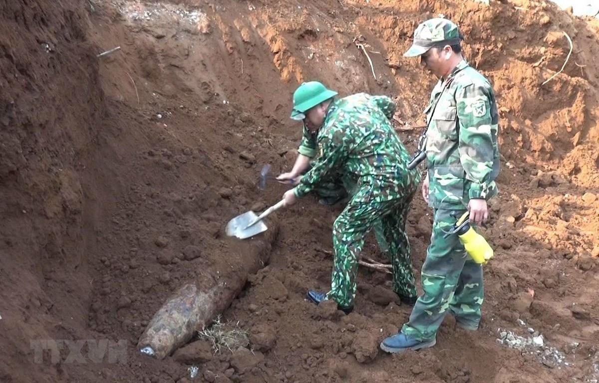 Lực lượng công binh xử lý quả bom được tìm thấy trong khu vực Trường Trung học phổ thông Cửa Tùng. (Ảnh: Nguyên Lý/TTXVN)