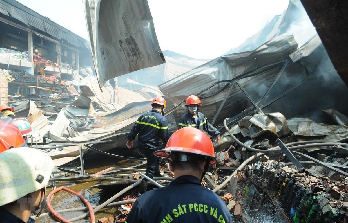 Lực lượng cứu hỏa phun nước dập tắt đám cháy. (Ảnh: Thành Chung/TTXVN)