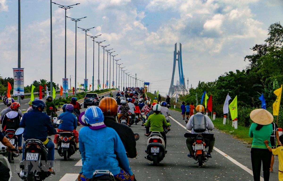 Người dân lưu thông qua cầu Vàm Cống sau khi thông xe. (Ảnh: Thanh Liêm/TTXVN)