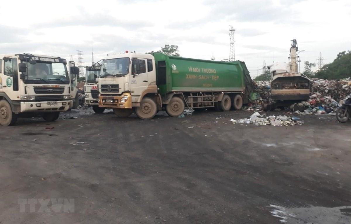 Công ty CP dịch vụ môi trường Thăng Long đang huy động tối đa phương tiện, nhân lực để thu dọn rác tồn đọng trên địa bàn quận Hoàng Mai. Ảnh Mạnh Khánh/TTXVN)