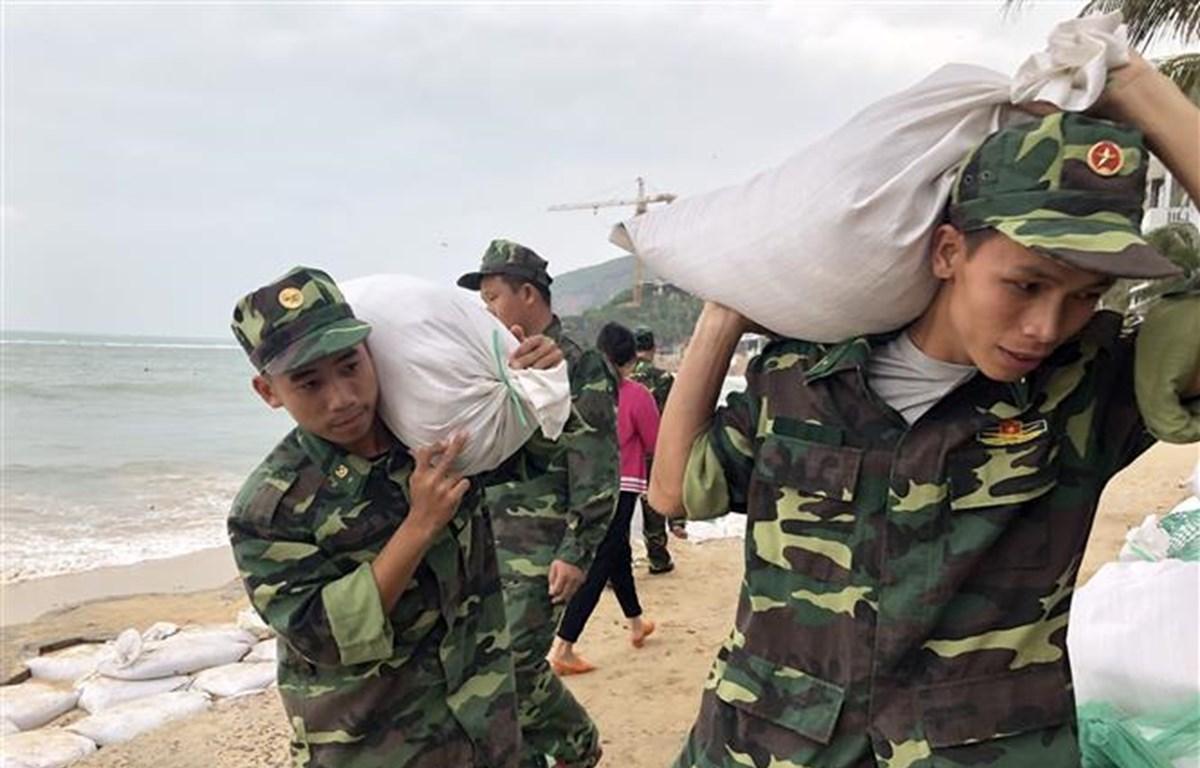 Lực lượng vũ trang tại tỉnh Bình Định vận chuyển bao tải cát giúp người dân xã Nhơn Hải, thành phố Quy Nhơn gia cố nhà cửa chống bão số 6. (Ảnh: Nguyên Linh/TTXVN)