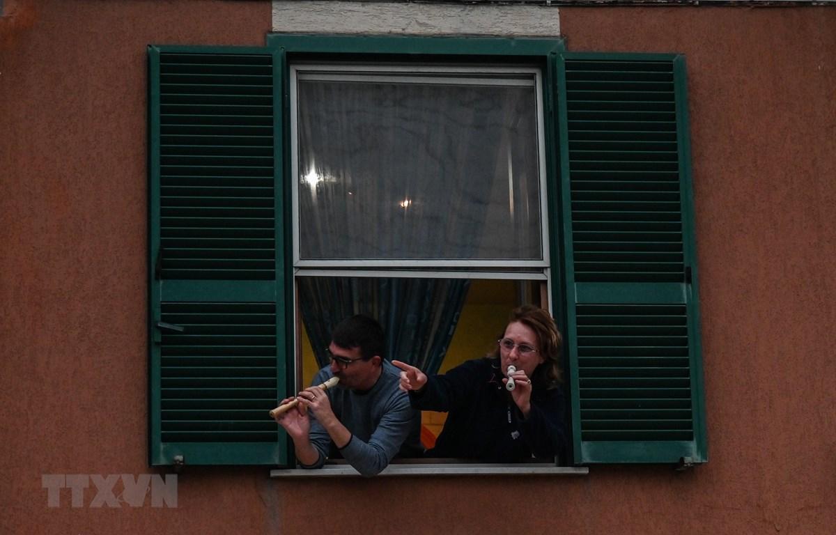Người dân Italy tham gia sự kiện Flashmod âm nhạc trên ban công nhằm thể hiện tinh thần đoàn kết quyết tâm đẩy lui dịch bệnh COVID-19 tại Rome. (Ảnh: AFP/TTXVN)