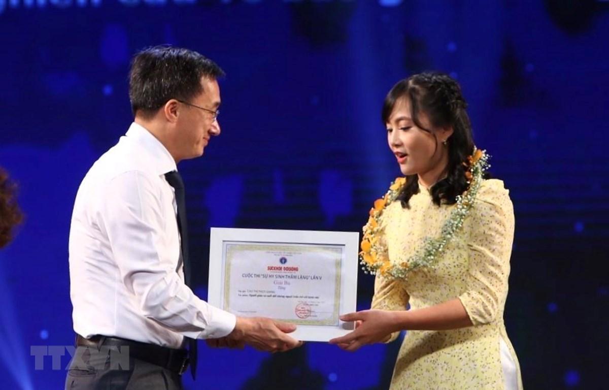 Ban tổ chức trao giải Nhì cho tác giả Cao Thùy Giang, báo Điện tử VietNamPlus. (Ảnh: Minh Quyết/TTXVN)