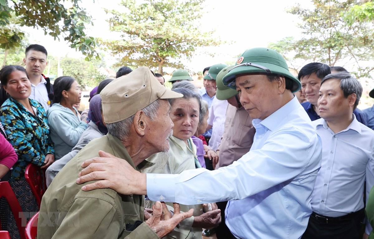 Thủ tướng Nguyễn Xuân Phúc thăm hỏi, chia sẻ khó khăn, mất mát với nhân dân thôn Đồng Tư, xã Hiền Ninh, huyện Quảng Ninh, tỉnh Quảng Bình. (Ảnh: Thống Nhất/TTXVN)