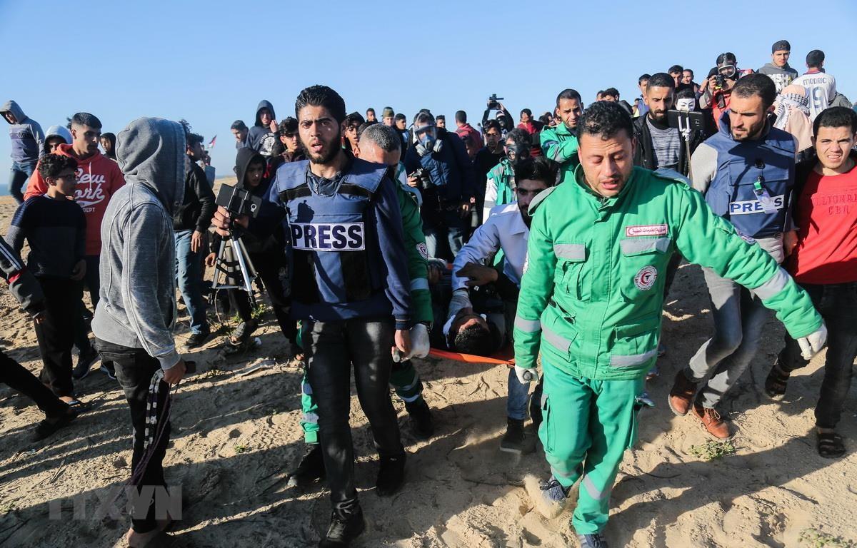 Nhân viên y tế chuyển người biểu tình Palestine bị thương tại Dải Gaza, ngày 19/3 vừa qua. (Ảnh: THX/TTXVN)
