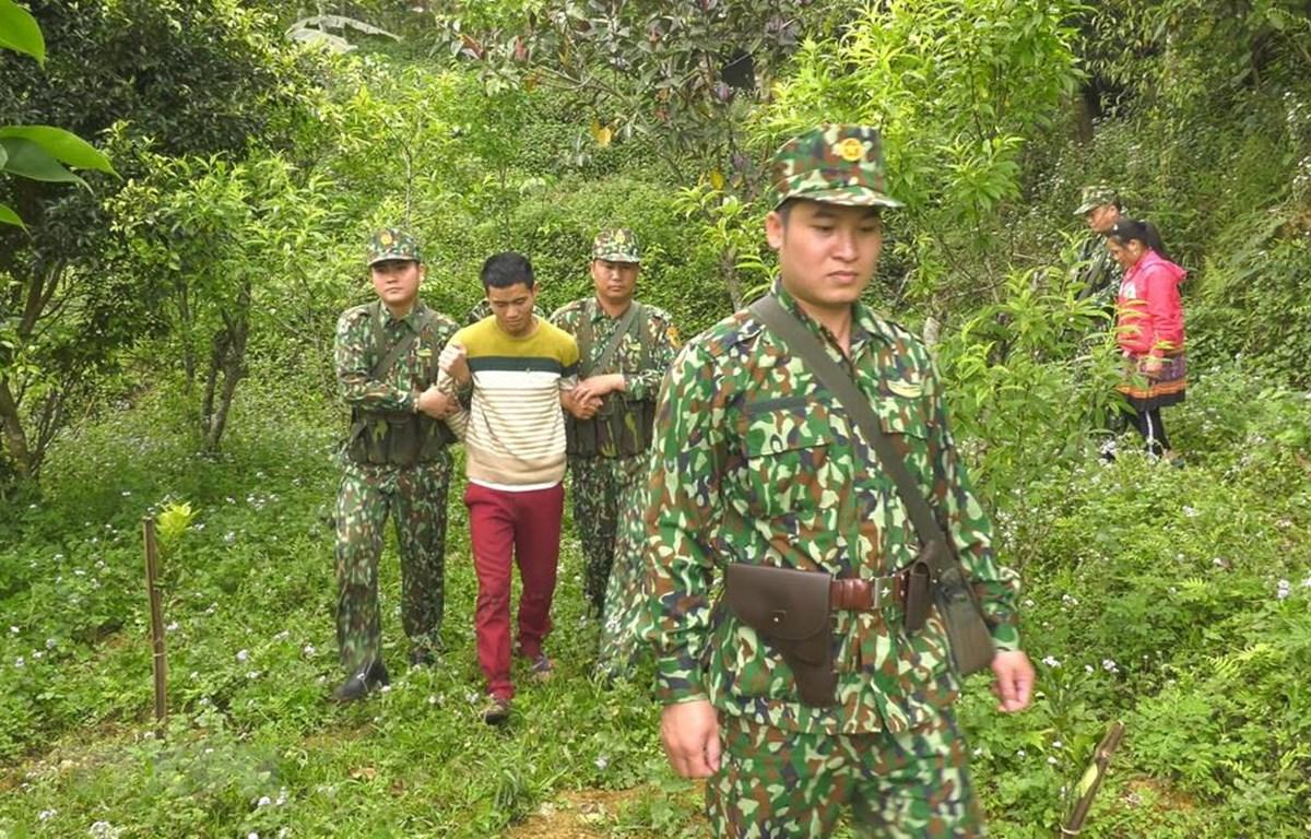 Lực lượng biên phòng áp giải đối tượng Ly Seo Ca tại khu vực biên giới. (Ảnh: TTXVN)