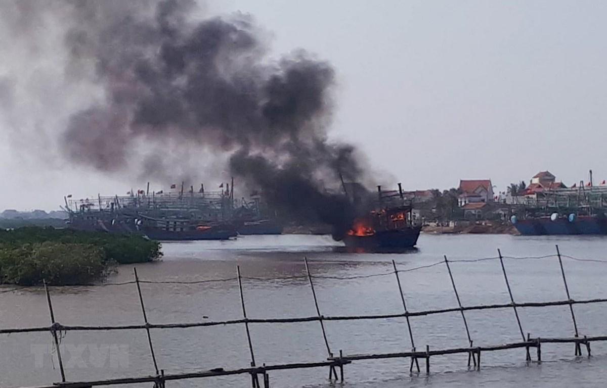 Tàu cá cháy ngùn ngụt tại khu vực cảng Lạch Quèn. (Ảnh: TTXVN phát)