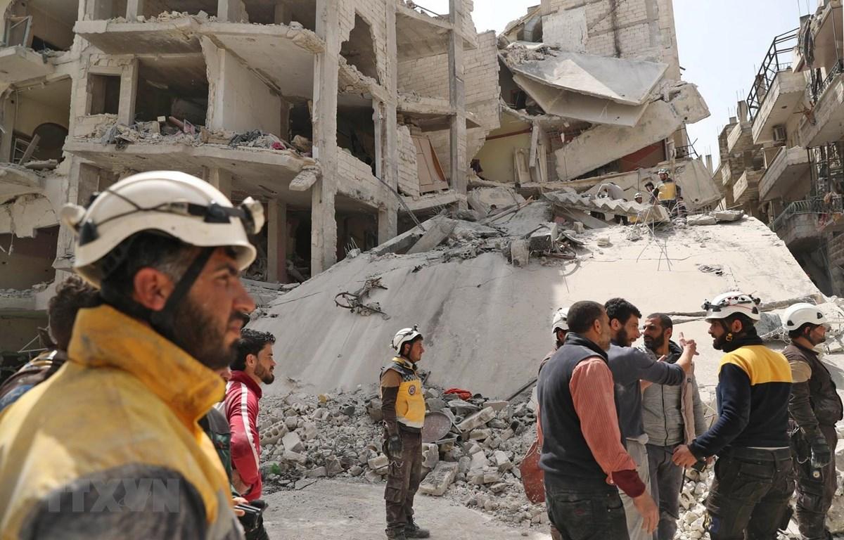 Nhân viên phòng vệ dân sự Syria tìm kiếm các nạn nhân tại khu vực nhà bị sập sau vụ nổ ở Jisr al-Shughur, tỉnh Idlib ngày 24/4. (Ảnh: AFP/TTXVN)