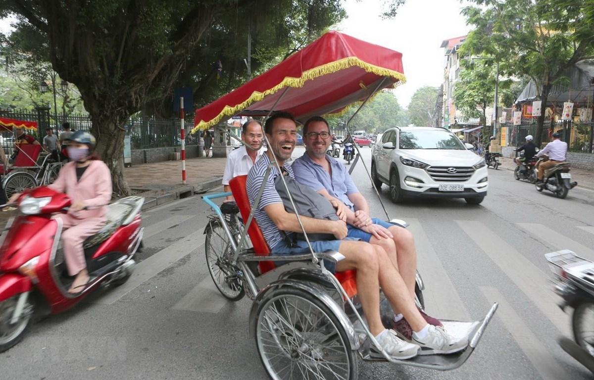Khách du lịch thích thú khi trải nghiệm phương tiện xích lô trên đường phố Hà Nội. (Ảnh: Thành Đạt/TTTXVN)