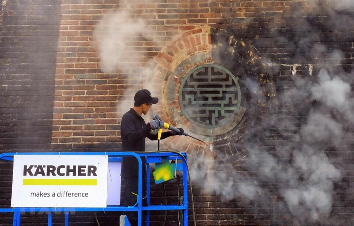 Các chuyên gia Karcher làm sạch di tích cổng Ngọ Môn, Đại nội Huế bằng công nghệ hơi nước nóng. (Ảnh: Quốc Việt/TTXVN)
