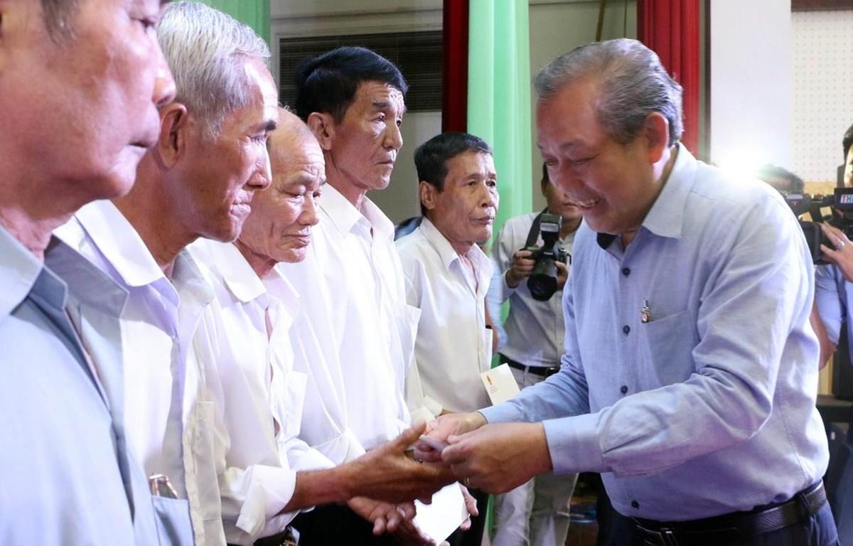 Phó Thủ tướng Thường trực Trương Hòa Bình trao quà cho các gia đình chính sách. (Ảnh: Trần Thị Thu Hiền/TTXVN)