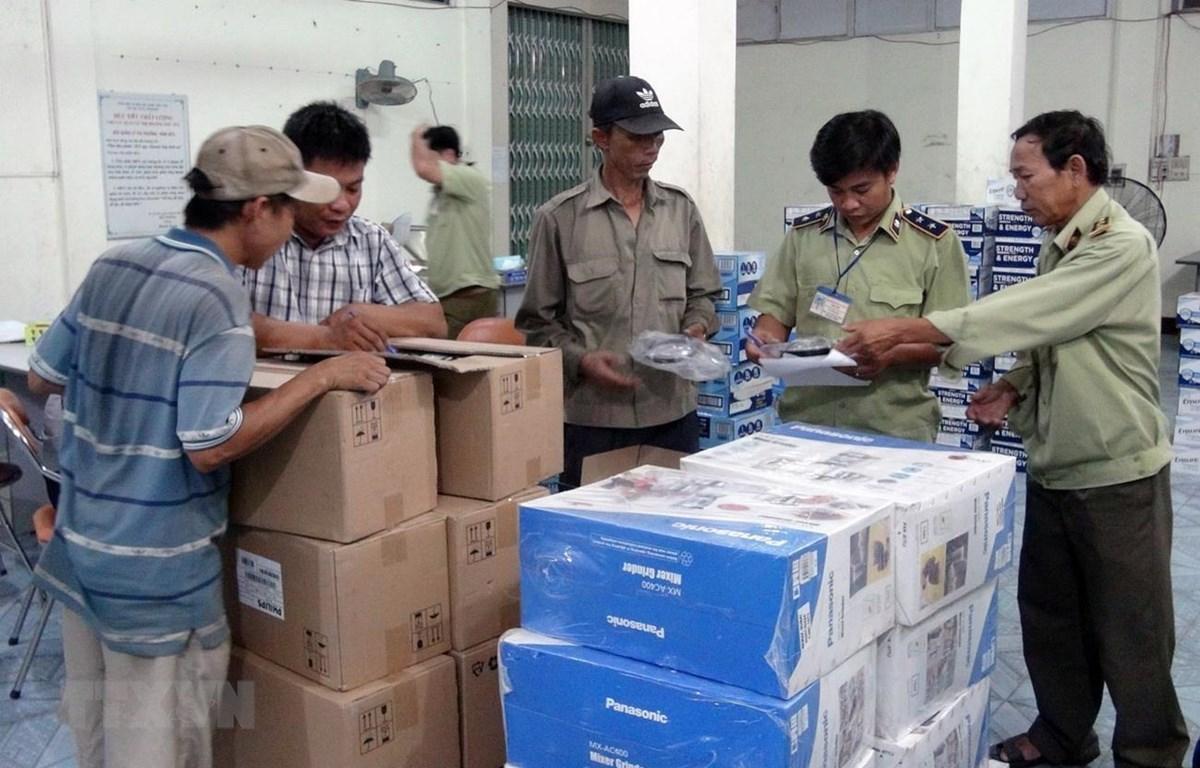 Lực lượng chức năng kiểm tra lô hàng hóa vừa bị bắt giữ. (Ảnh: Thế Lập/TTXVN)