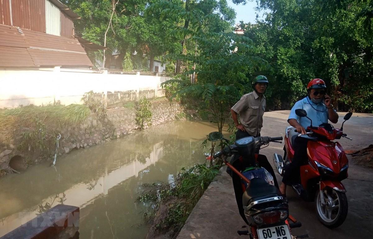 Hiện trường nơi hai em học sinh bị tai nạn đường cong, tiếp giáp với suối và không có rào chắn. (Ảnh: Sỹ Tuyên/TTXVN)