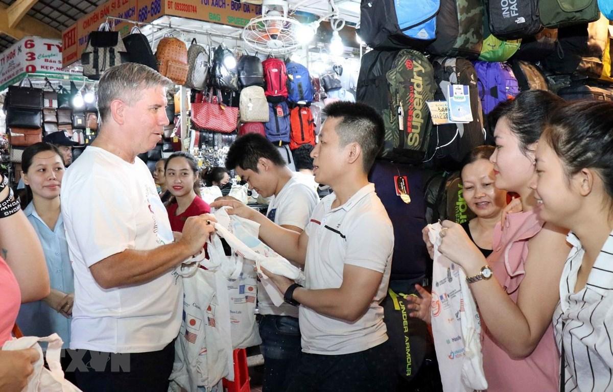 Các Tổng lãnh sự tại Thành phố Hồ Chí Minh tham gia tặng túi vải tái sử dụng cho tiểu thương và người đi chợ Bến Thành. (Ảnh: Xuân Khu/TTXVN)
