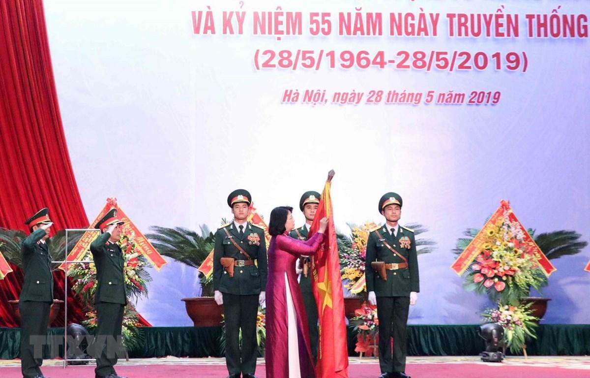 Phó Chủ tịch nước Đặng Thị Ngọc Thịnh gắn Danh hiệu Anh hùng Lực lượng Vũ trang Nhân dân lên lá cờ truyền thống của Cục Đối ngoại. (Ảnh: Văn Điệp/TTXVN)