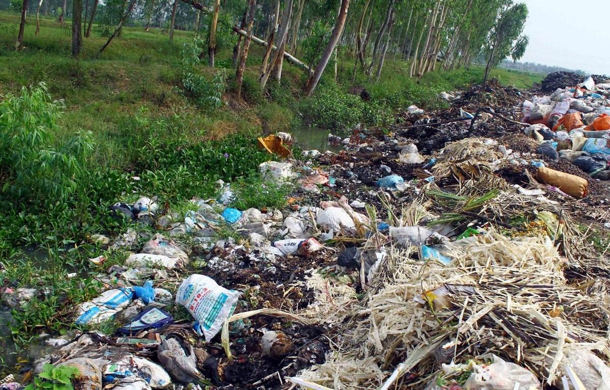 Lượng rác quá tải, chất thành từng đống tràn xuống cả kênh mương nước thủy lợi gây tắc nguồn nước và tràn ra đồng ruộng xung quanh. (Ảnh: Tá Chuyên/TTXVN)