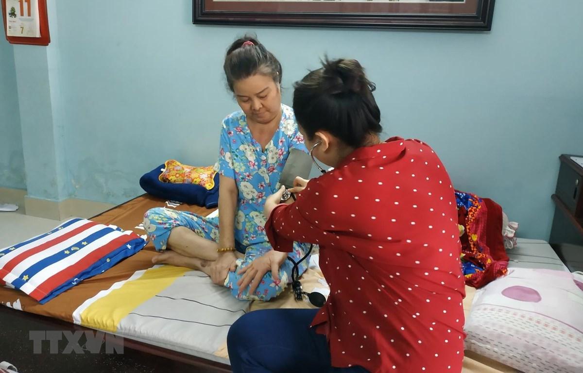 Bác sỹ bệnh viện Ung bướu Thành phố Hồ Chí Minh khám bệnh tại nhà cho bệnh nhân ung thư tại quận 2. (Ảnh: Đinh Hằng/TTXVN)