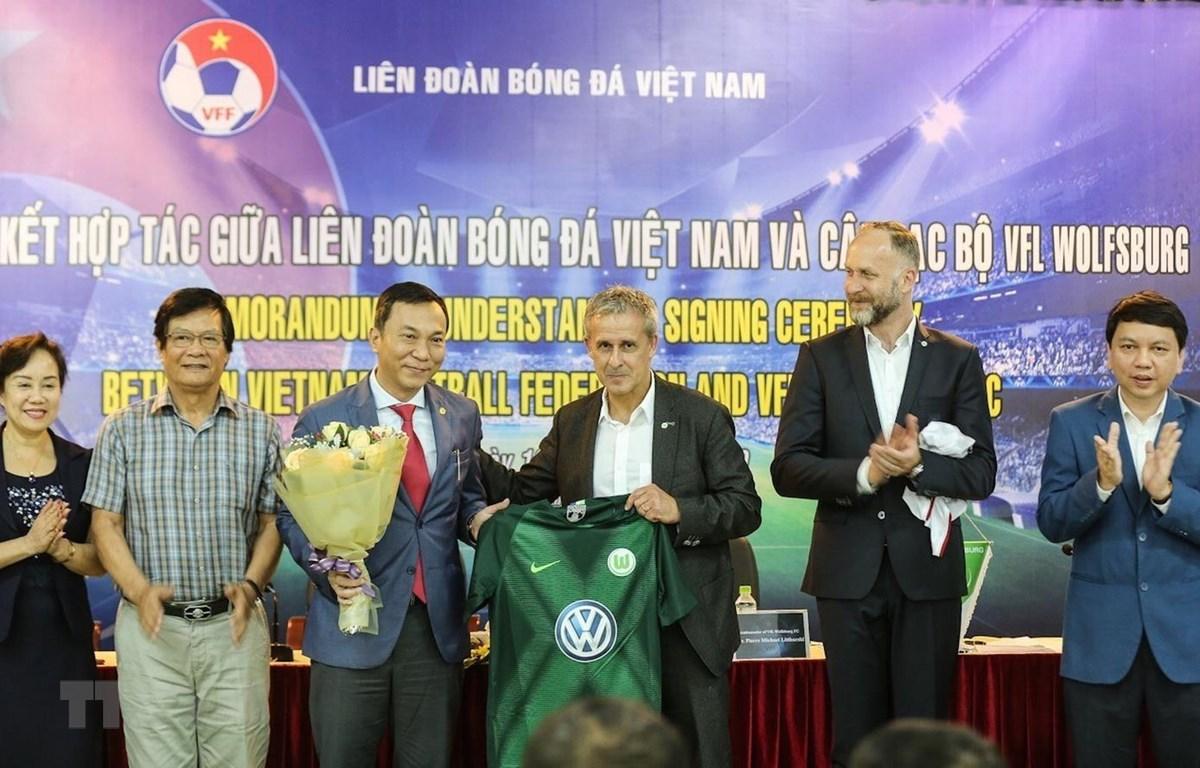Ông Pierre Michael Littbarski, huyền thoại bóng đá Đức, Đại sứ CLB Wolfsburg tặng áo đấu của CLB Wolfsburg cho ông Trần Quốc Tuấn, Phó Chủ tịch thường trực VFF. (Ảnh: Trọng Đạt/TTXVN)