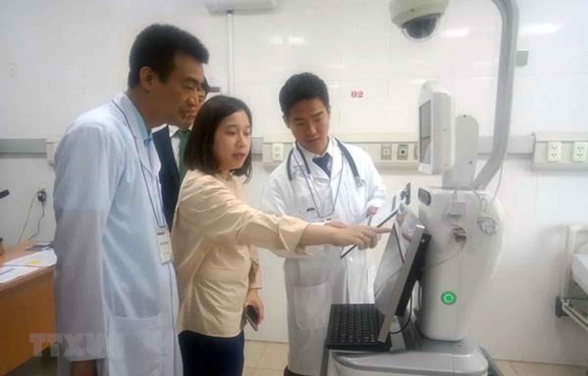 Chuyên gia Nhật Bản giới thiệu, hướng dẫn sử dụng robot chăm sóc tại buồng bệnh. (Ảnh: Hoàng Ngọc/TTXVN)