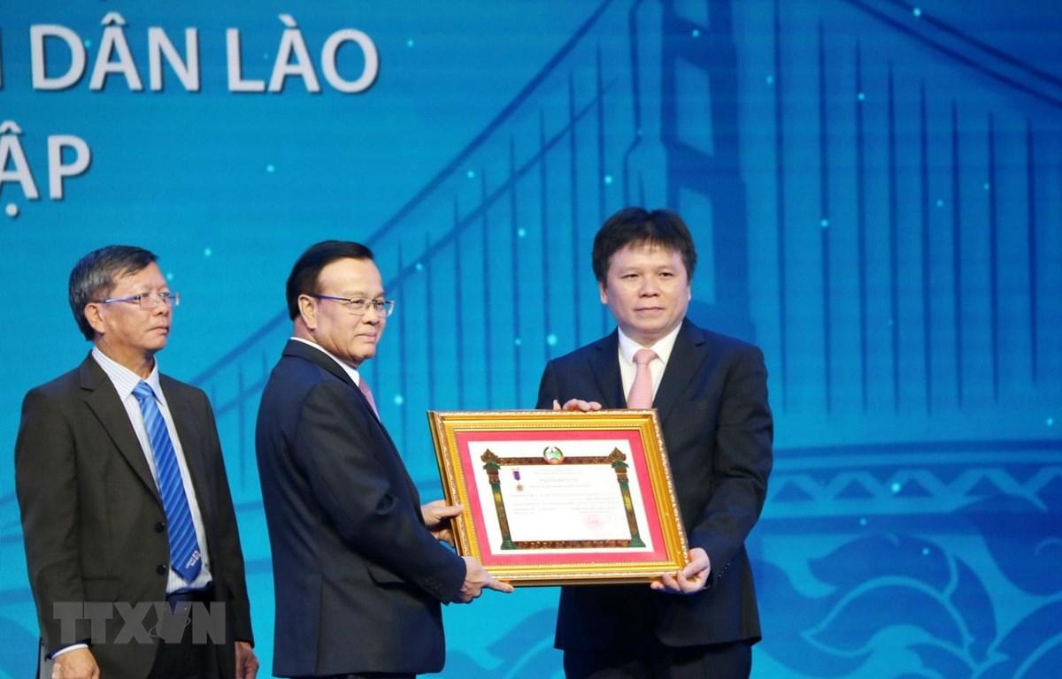 Phó Thủ tướng chính phủ Lào Somdee Duangdee (giữa) trao tặng Huân chương Lao động hạng Nhất cho LaoVietBank. (Ảnh: Xuân Tú/TTXVN)