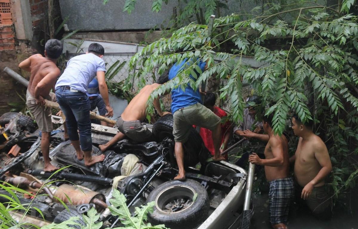 Người dân cố gắng cứu người bị nạn ra khỏi chiếc xe bị nạn. (Ảnh: Huỳnh Phúc Hậu/TTXVN)