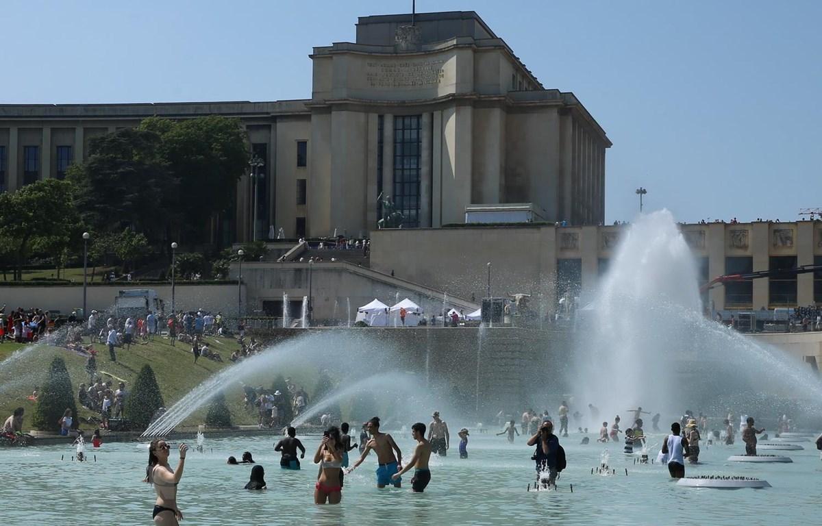 Trong ảnh: Người dân giải nhiệt tại một đài phun nước ở Paris ngày 26/6. Ảnh: THX/TTXVN