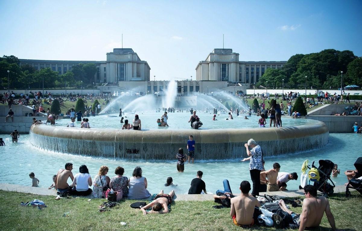 Người dân tránh nắng nóng bên vòi phun nước tại Paris của Pháp, ngày 26/6 vừa qua. (Ảnh: THX/TTXVN)