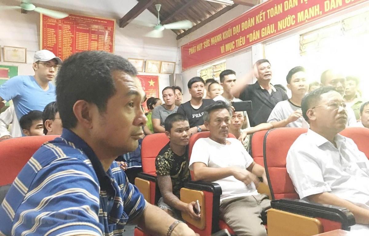 Ông Nguyễn Phước Quy Phong, Phó Tổng Giám đốc công ty CP vận tải và thương mại Quốc tế - chủ tàu hàng Pacific 01 (áo kẻ xanh) đối thoại với người thân các nạn nhân. (Ảnh: TTXVN phát)