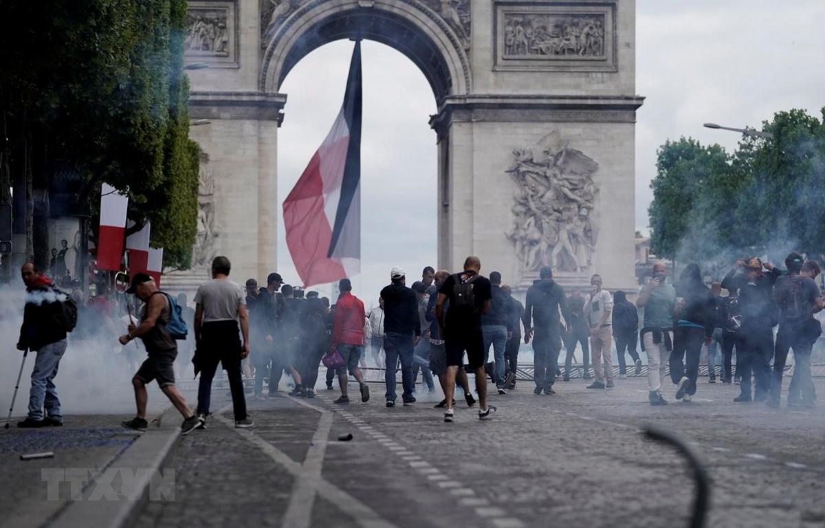 Cảnh sát phun hơi cay để giải tán đám đông người biểu tình quá khích tại đại lộ Champs Elysees ở thủ đô Paris, Pháp, ngày 14/7. (Ảnh: AFP/TTXVN)
