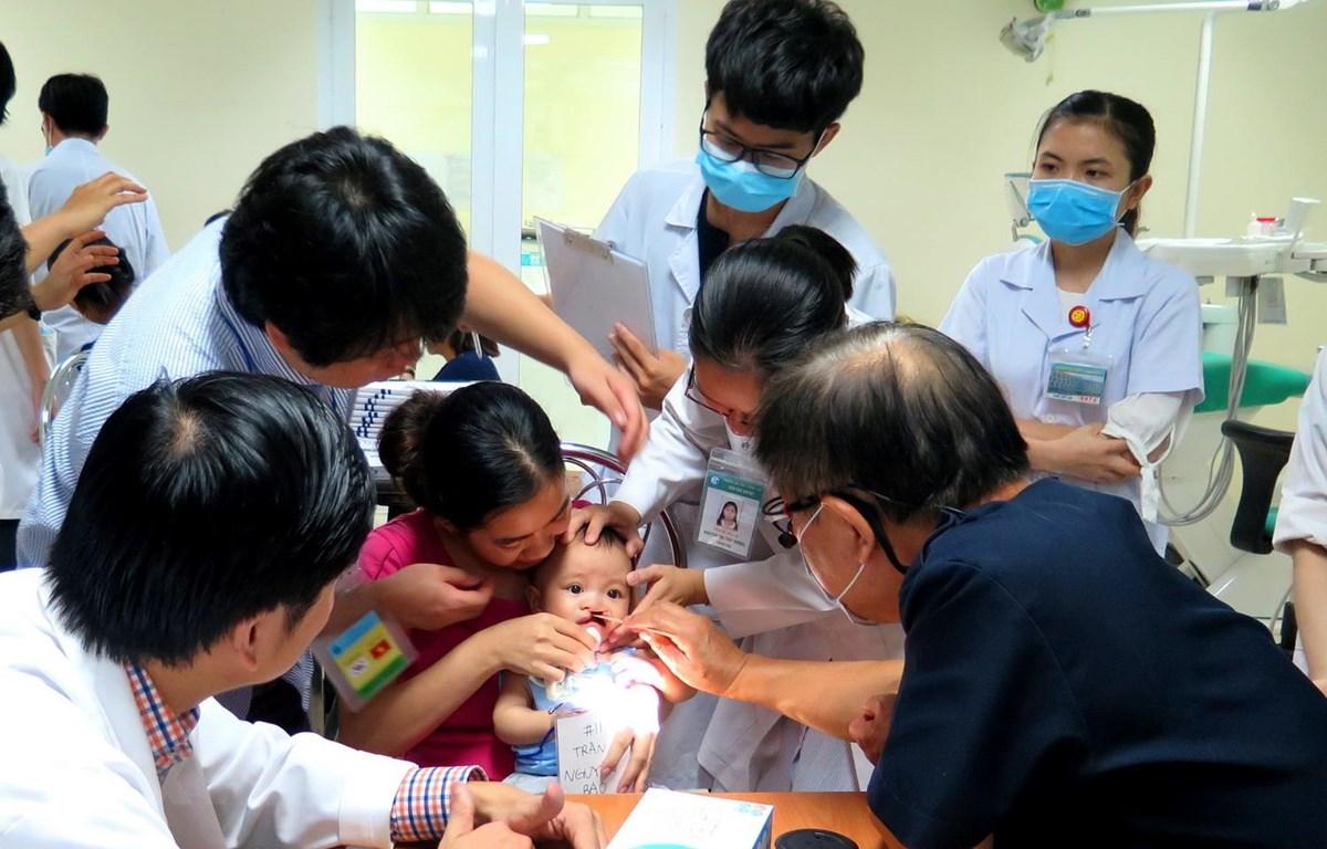 Các giáo sư, bác sỹ khám, điều trị và phẫu thuật miễn phí cho trẻ em bị sứt môi, hở hàm ếch, sẹo xấu ở mũi, khe hở ngang mặt. (Ảnh: Tường Vi/TTXVN)