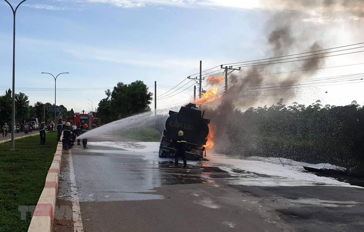Lực lượng cảnh sát Phòng cháy chữa cháy chữa cháy xe bồn chở dầu biể kiểm soát AX-1026 tại hiện trường. (Ảnh: TTXVN phát)