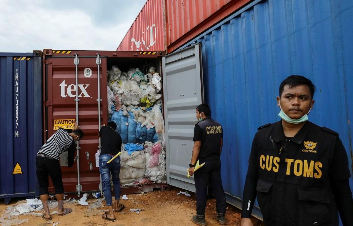 Nhân viên Hải quan Indonesia kiểm tra container chứa rác thải nhựa tại cảng Batu Ampar ở Batam, ngày 15/6 vừa qua. (Ảnh: AFP/TTXVN)