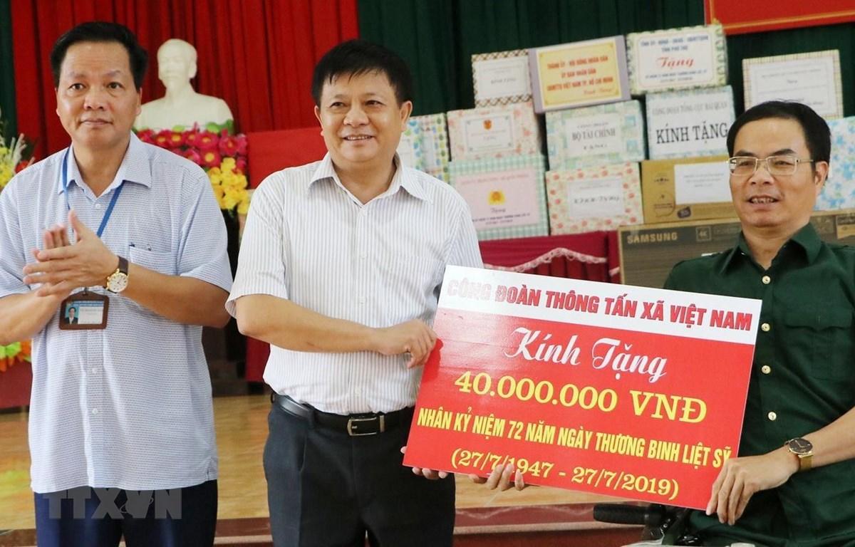 Phó Tổng giám đốc Thông tấn xã Việt Nam Đinh Đăng Quang trao tặng quà đến các thương, bệnh binh tại Trung tâm điều dưỡng người có công tỉnh Phú Thọ. (Ảnh: Trung Kiên/TTXVN)