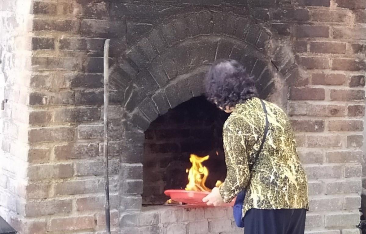 Người dân đốt vàng mã tại Đình Ứng Thiên, quận Đống Đa, Hà Nội. (Ảnh: Minh Nghĩa/TTXVN)