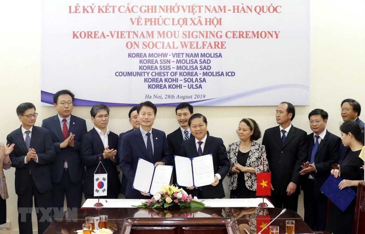 Thứ trưởng Bộ Lao động-Thương binh và Xã hội Lê Tấn Dũng và Thứ trưởng Bộ Y tế và Phúc lợi xã hội Hàn Quốc Ganglip Kim ký kết Bản ghi nhớ hợp tác trong lĩnh vực phúc lợi xã hội. (Ảnh: Anh Tuấn/TTXVN)