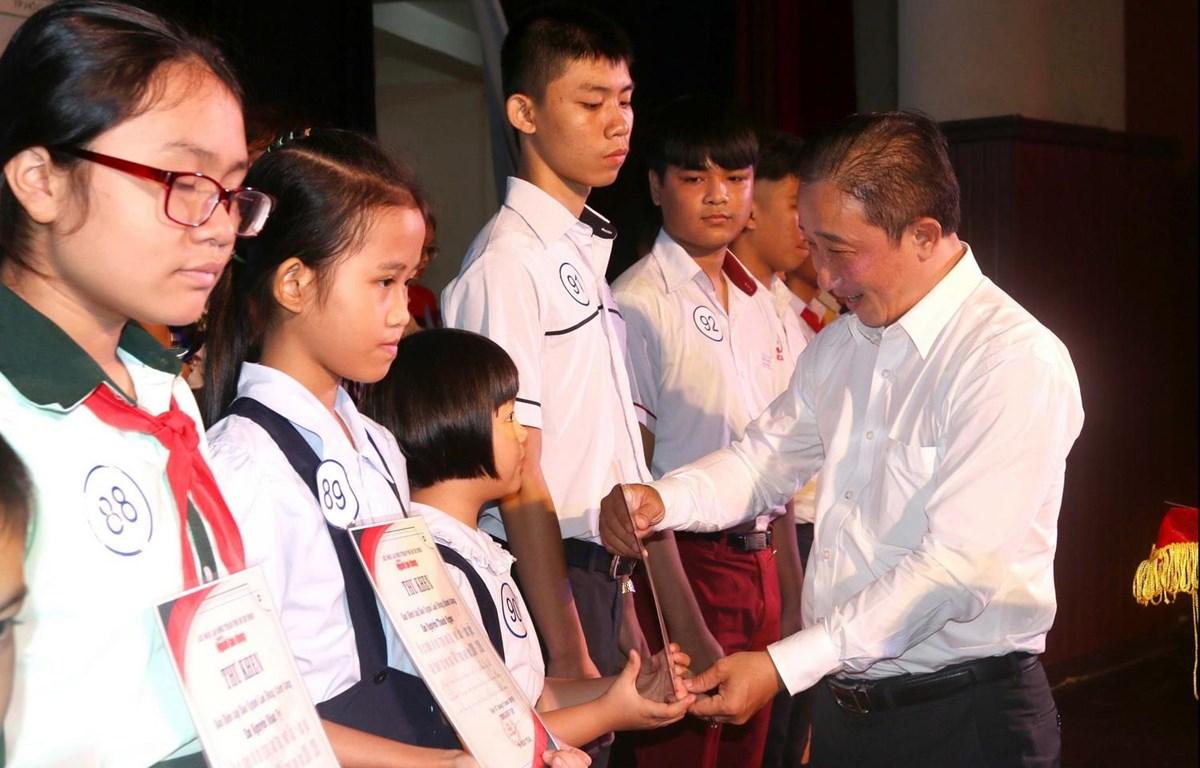 Ông Bùi Thanh Liêm, Phó Tổng Biên tập Báo Người Lao Động trao học bổng cho con em công nhân lao động có hoàn cảnh khó khăn. (Ảnh: Thanh Vũ/TTXVN)