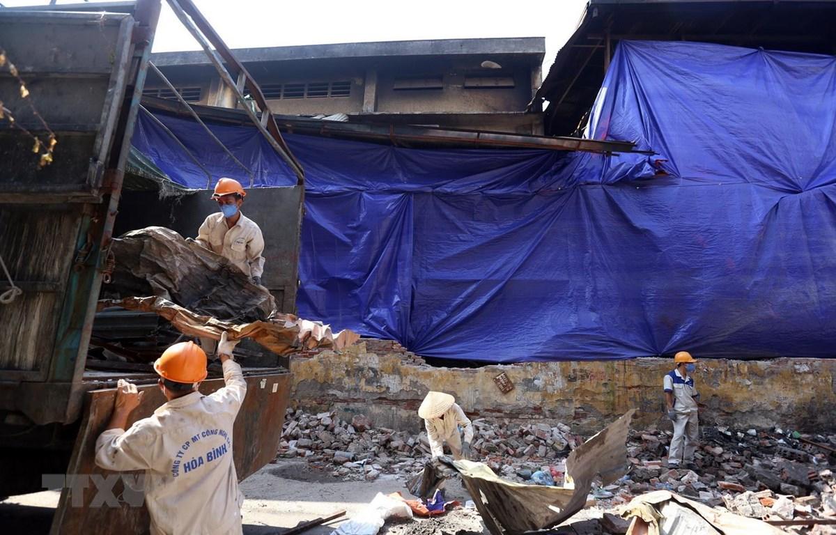 Công nhân Công ty cổ phần môi trường công nghệ cao Hòa Bình dọn dẹp vệ sinh tại khu vực nhà kho của Công ty Rạng Đông. (Ảnh: Huy Hùng/TTXVN)
